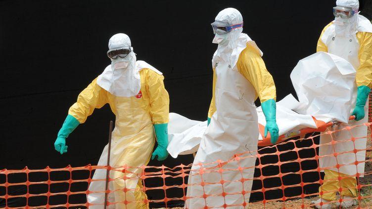 Des médecins de Médecins sans frontières (MSF) transportent le corps d'une personne morte de la fièvre Ebola, àGuékédou (Guinée), le 1er avril 2014. (SEYLLOU / AFP)