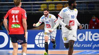 Le joueur de l'équipe de France de handball,Ludovic Fabregas (au centre), fête un but lors de la victoire des Français contre la Norvège au championnat du monde en Egypte, le 14 janvier 2021 au Caire. (ANNE-CHRISTINE POUJOULAT / POOL)
