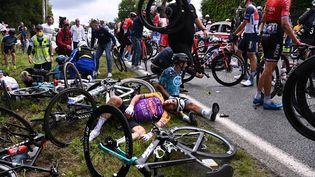 Des coureurs à terre après la chute causée par une spectatrice lors de la première étape du Tour de France entre Brest et Landerneau, samedi 26 juin 2021. (ANNE-CHRISTINE POUJOULAT / AFP)