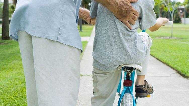 Un homme aide un petit garçon à faire du vélo. (illustration) (LAURENCE MOUTON / MAXPPP)