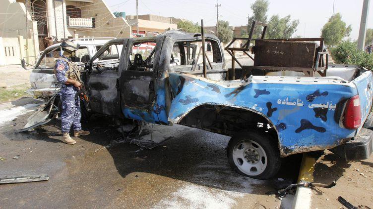 Un policier inspecte un véhicule à Kirkouk, à 250 km au nord de Bagdad, après un attentat le 15 juillet 2013. L'Irak est confronté à une vague de violences. (© STRINGER IRAQ / REUTERS / X80014)