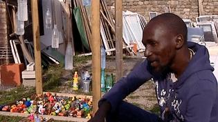 """L'artiste Abou Sidibé à côté de son installation / """"Festival Images et paroles d'Afrique""""  (France 3 / capture d'écran)"""