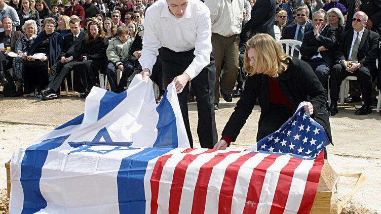 Des drapeaux israélien et américain sont déposés, le 9 mars 2003, à Haïfa (Israël), sur le cercueil d'une victime israélo-américaine d'un attentat commis par un Palestinien. (RONI SCHUTZER / YEDIOTH AHARONOTH / AFP)