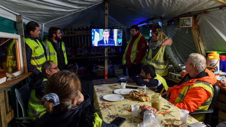 """Des """"gilets jaunes"""" regardent l'allocution d'Emmanuel Macron, sous une tente, au Mans (Sarthe), le 10 décembre 2018. (JEAN-FRANCOIS MONIER / AFP)"""