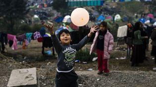 """Un enfant joue avec un ballon dans le camp d'Idomeni. Certaines associations tentent de proposer des activités aux enfants. Mais pour Médecins sans Frontières, la """"priorité c'est de leur donner à manger, de les soigner et de les aider à survivre."""" (DIMITAR DILKOFF / AFP)"""