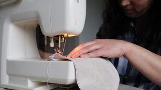 Une femme fabrique un masque en tissu avec une machine à coudre (illustration). (GREGORY YETCHMENIZA / MAXPPP)