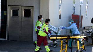 Du personnel médical transporte un patient aux urgences de l'hôpital de Madrid (Espagne), le 26 mars 2020. (JUAN CARLOS LUCAS / NURPHOTO / AFP)