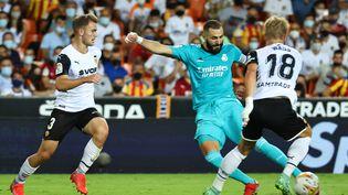 Karim Benzema (Real Madrid) tente de frapper devant Daniel Wass (Valence) en Liga, au Stade Mestella, le 19 septembre 2021 (JOSE JORDAN / AFP)