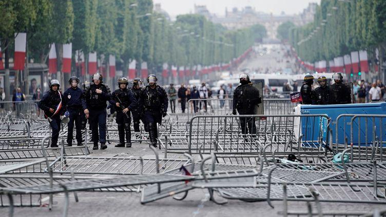 Des CRS sur l'avenue des Champs-Elysées, à Paris, le 14 juillet 2019. (KENZO TRIBOUILLARD / AFP)