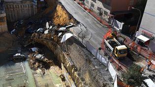 Des voitures sont immobilisées dans un cratère, le 15 février 2018, au lendemain de l'effondrement d'une chaussée à Rome (Italie). (TIZIANA FABI / AFP)