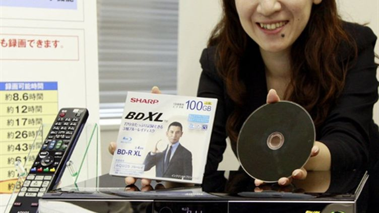 Une employée de Sharp présente le nouveau disque Blu-ray triple couche, à Tokyo, le 16 juillet 2010. (AFP PHOTO / Yoshikazu TSUNO)