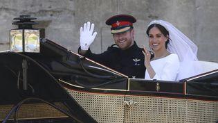 Le prince Harry et Meghan Markle saluent la foule après leur mariage à la chapelle Saint Georges, le 19 mai 2018, à Windsor. (STEVE PARSONS / AFP)
