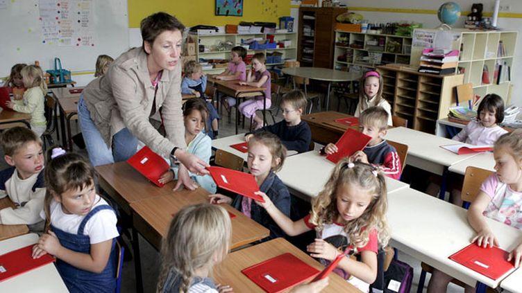 (Illustration : une institutrice d'Hebecrevon distribuant des cahiers à ses jeunes élèves © MaxPPP)