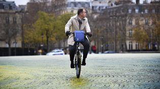 Un homme à vélo place de l'Etoile à Paris le 11 décembre 2015. (MARTIN BUREAU / AFP)