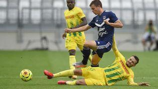 Le BordelaisNicolas De Preville et le NantaisPedro Chirivella (à terre), lors de la rencontre entre leur deux clubs, pour la reprise de la Ligue 1, à Bordeaux (Nouvelle-Aquitaine), le 21 août 2020. (NICOLAS TUCAT / AFP)
