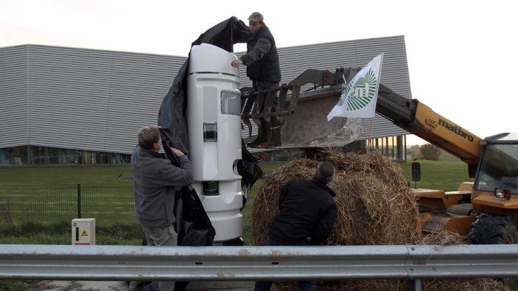 Des agriculteurs recouvrent une borne écotaxe, le 22 octobre 2013 à Eslettes (Seine-Maritime). (CHARLY TRIBALLEAU / AFP)