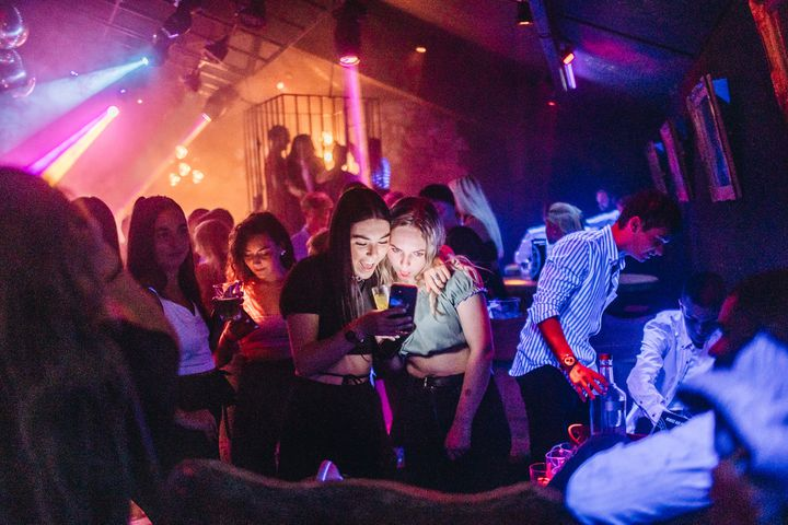 Deux amies consultent leur téléphone près des tables réservées aux groupes achetant des bouteilles d'alcool. (PIERRE MOREL / FRANCEINFO)
