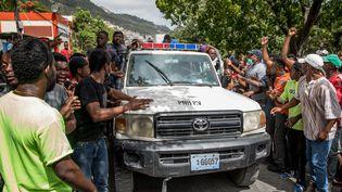Des habitants de Port-au-Prince (Haïti) saluent le passage d'une voiture de police, le 8 juillet 2021. (VALERIE BAERISWYL / AFP)