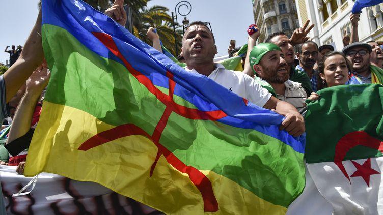 Des manifestants algériens brandissent les drapeaux national et amazigh à Alger, le 21 juin 2019. (RYAD KRAMDI / AFP)