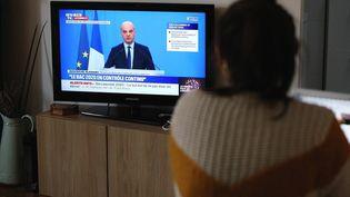 Une enseignante regarde à la télévision le ministre de l'Education nationale,Jean-Michel Blanquer, annoncer que le bac 2020 se fera entièrement en contrôle continu, le 3 avril 2020 à Paris. (ADNAN FARZAT / NURPHOTO / AFP)