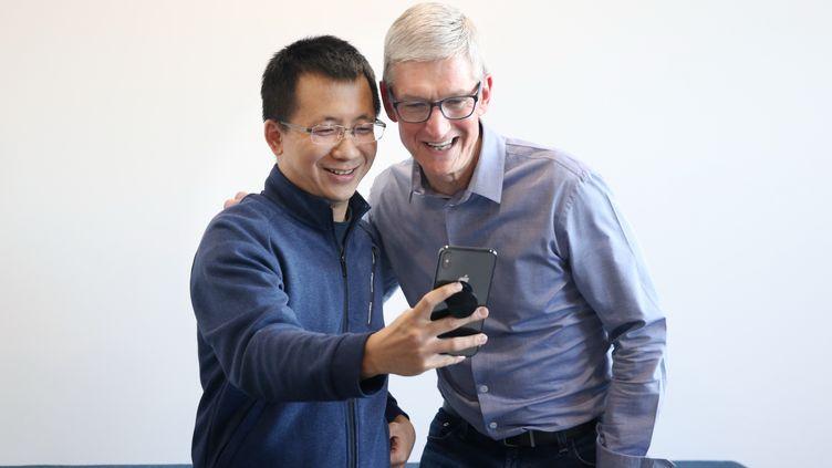 Zhang Yimin, le patron du groupe chinois ByteDance (à gauche), avec Tim Cook, le directeur général d'Apple (à droite), se filment pour l'appli Tik Tok (Pékin, 11 octobre 2018) (BYTEDANCE / IMAGINECHINA / AFP)