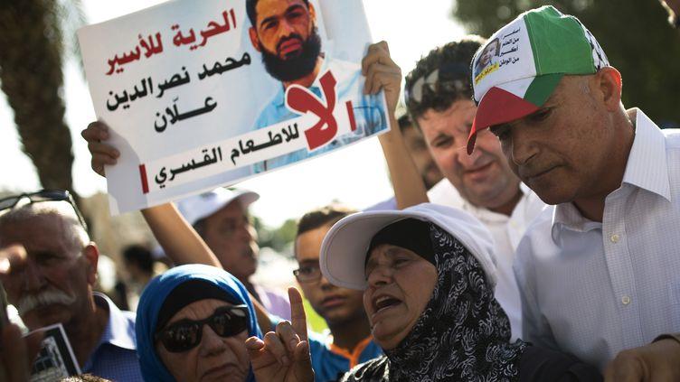 Maazouzeh Allan, la mère de Mohammed Allan, brandit un portrait de son fils en grève de la faim,à Beersheba dans le sud d'Israël, le 9 août 2015. (AMIR COHEN / REUTERS )