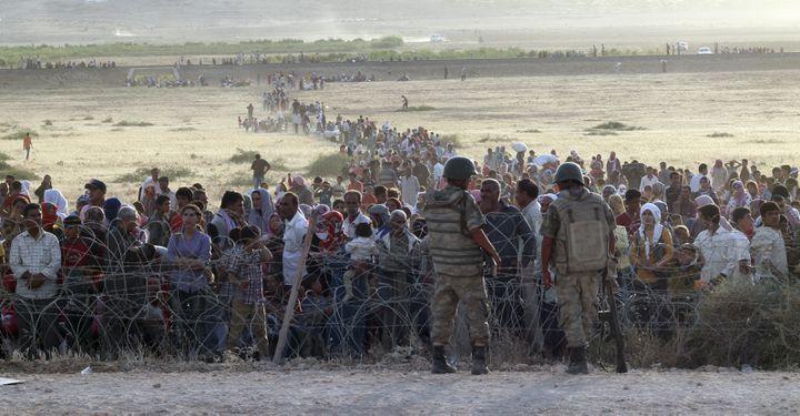 Des réfugiés kurdes de Kobani attendent l'autorisation d'entrer en Turquie, le 18 septembre 2014 près de la ville de Suruc (Turquie). (REUTERS)