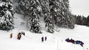 Des sauveteurs sondent la neige le 4 janvier 2006 à la station pyrénéenne du Mourtis (Haute-Garonne), lors d'un exercice de sauvetage. (GEORGES GOBET / AFP)