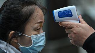 Une femme portant un masque se faisant contrôler la température à Wuhan, le 2 avril. (HECTOR RETAMAL / AFP)