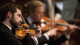 Des violonistes d'un orchestre. (BEN EDWARDS / GETTY IMAGES)