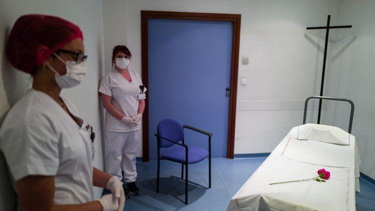 Des agents des services mortuaires posent à côté d'un brancard à la morgue de l'hôpital Emile-Muller à Mulhouse (Haut-Rhin), le 22 avril 2020. (SEBASTIEN BOZON / AFP)