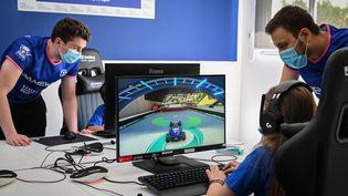Des animateurs donnent des instructions aux enfants qui jouent aux jeux vidéo lors d'un cours d'été gratuit esport pour les jeunes à Boulogne-Billancourt, le 22 juillet 2020. (BERTRAND GUAY / AFP)