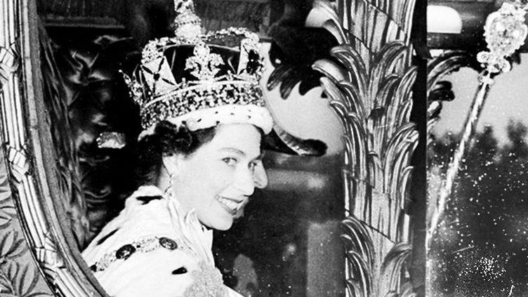La reine Elisabeth II, dans le carrosse royal, peu de temps après son couronnement à l'abbaye de Westminster, le 2 juin 1953. (STF / INP / AFP)