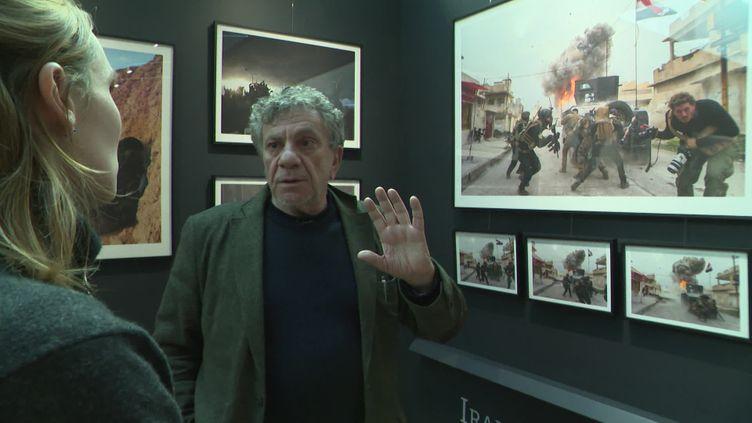 Patrick Chavel devant une photo prise à Mossoul en 2016 alors qu'il accompagne son fils Antoine sur le terrain. Mémorial de Caen. (C. Lefrançois / France Télévisions)