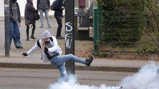 Une jeune étudiante rejete un gaz lacrymogène, lors d'une manifestation contre la loi Travail à Nantes le 24 mars 2016. (FRANCK DUBRAY / MAXPPP)