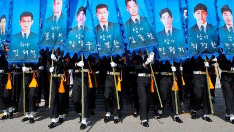 Les gardes d'honneur sud-coréens défilent dans le centre-ville de Daejeon, le 26 Mars 2013. Ils portent des banderoles à l'effigie des 46 marins morts en 2010, lorsque le navire de guerre le «Cheonan» a coulé. (AFP PHOTO / POOL / KIM Jae-Hwan   )