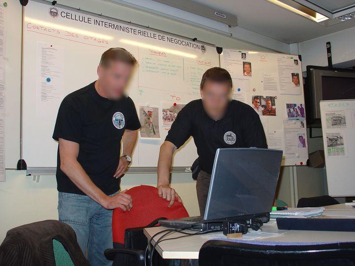 Deux officiers du Raid et du GIGN au PC installé sur le site de la gendarmerie à Satory, près de Versailles, lors d'une des 22 missions menées par la Cellule. (CELLULE INTERMINISTERIELLE DE NEGOCIATION)