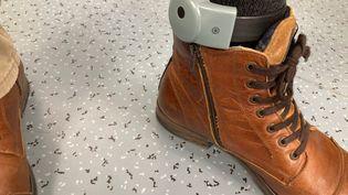 Un bracelet anti-rapprochement installé sur la cheville d'un homme. (MARGAUX STIVE / RADIO FRANCE)