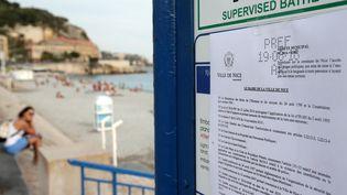 L'arrêté municipal interdisant le port du burkini affiché à l'entrée de la plage de Nice (Alpes-Maritimes), le 19 août 2016. (JEAN CHRISTOPHE MAGNENET / AFP)