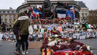 Des gens continuent de se recueillir sur la place de la République à Paris, le 13 décembre 2015, un mois après les attentats. (CHRISTOPHE PETIT TESSON / EPA)