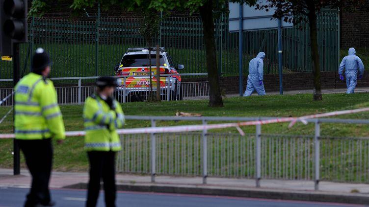 Des officiers de police ont formé un cordon de sécurité à Woolwich, dans l'est de Londres (Royaume-Uni), où deux hommes ont tué un militaire en civil avec un hachoir, le 22 mai 2013. (CARL COURT / AFP)