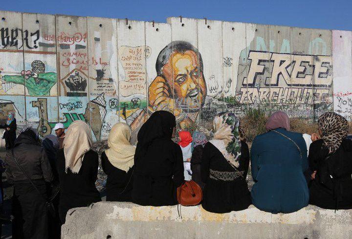 Des femmes palestiniennes, assises près du mur de séparation entre Ramallah et Jérusalem, sur lequel figure un dessin appelant à la libération du prisonnier Marwan Barghouti. (Abbas Momani-AFP)