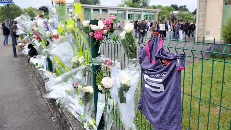 Un maillot du Stade rennais et des fleurs accrochés sur les grilles du collège de Cleunay, à Rennes (Ille-et-Vilaine), oùun adolescent de 13 ans est mort le 23 juin 2012, après une bagarre. (MARC OLLIVIER / OUEST FRANCE / MAXPPP)