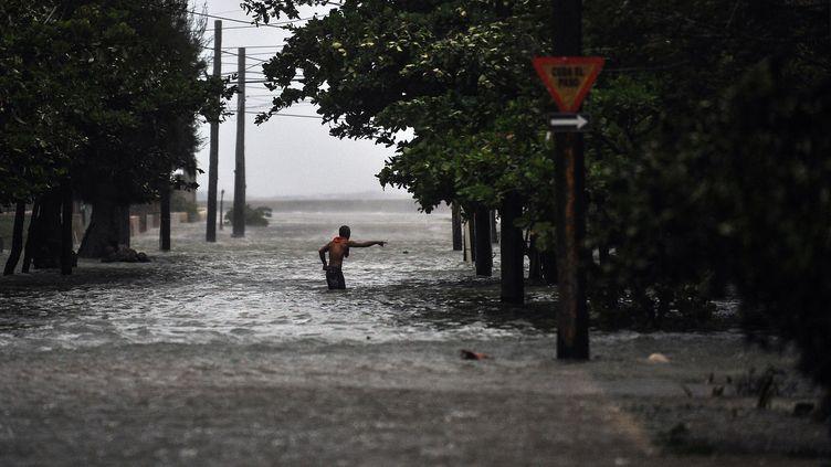 Un homme traverse une rue complètement inondée après le passage de l'ouragan Irma, à La Havane (Cuba), le 9 septembre 2017. (YAMIL LAGE / AFP)