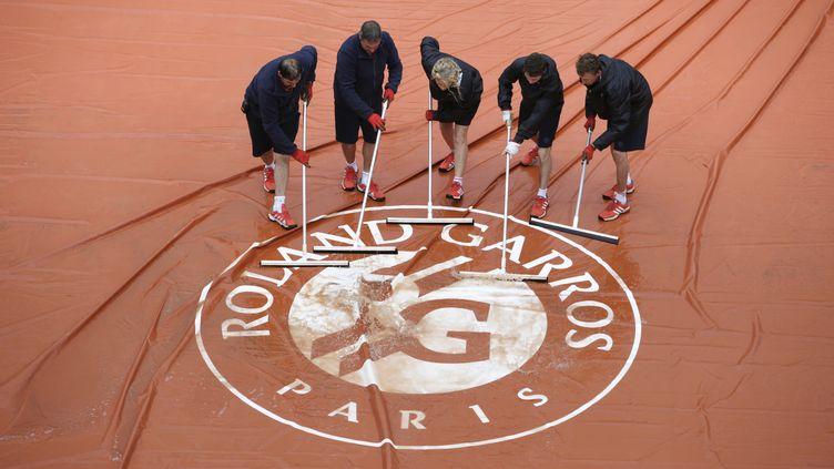 Un Roland-Garros sans pluie, c'est comme un été sans soleil. Comme souvent ces dernièrs jours, la pluie s'est invitée ce lundi porte d'Auteuil. (KENZO TRIBOUILLARD / AFP)