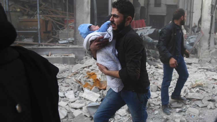 Un Syrien transporte un bébé dans les décombres d'Hamouria, dans l'est de la Ghouta, le 3 décembre 2017. (AMER ALMOHIBANY / AFP)
