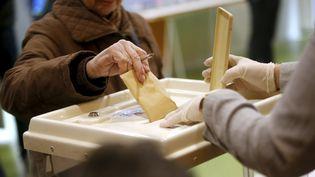 Une électrice vote au premier tour des élections municipales, dans le 6e arrondissement de Marseille, le 15 mars 2020. Le second tour aura lieu le 28 juin 2020. (VALLAURI NICOLAS / MAXPPP)