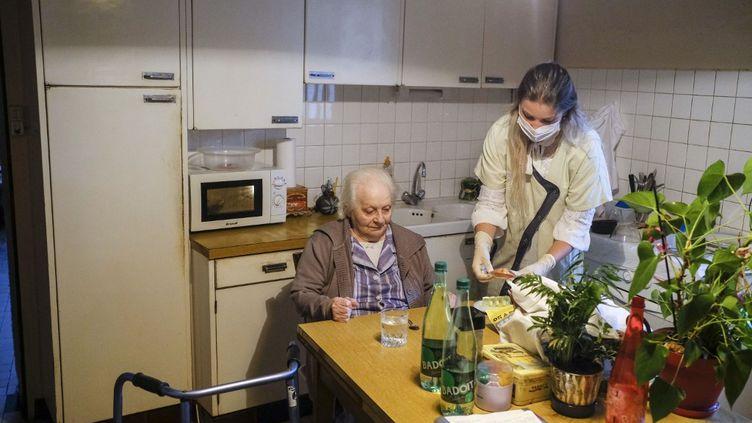 Une aide à domicile chez une personne âgée à Angers (Maine-et-Loire), le 22 septembre 2020. (JEAN-MICHEL DELAGE / HANS LUCAS / AFP)