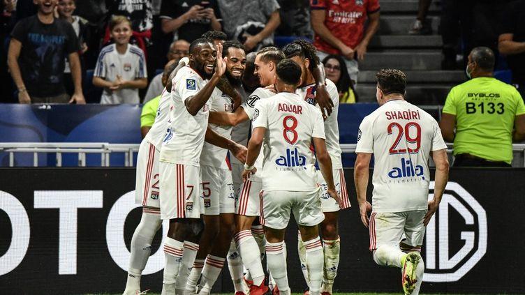 Les Lyonnais célèbrent le deuxième but de Jason Denayer face à Strasbourg, dimanche 12 septembre 2021. (JEFF PACHOUD / AFP)
