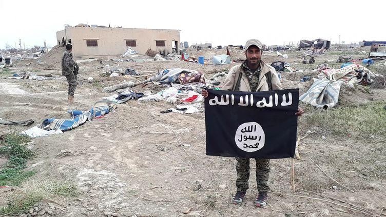 Un combattant arabe brandit fièrement un étendard du califat déchuqui flottait sur une position reprise aux jihadistes à Baghouz. (AURELIEN COLLY / RADIO FRANCE)
